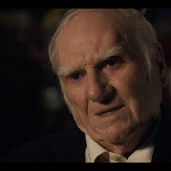 A headshot of an elderly man, photographed in a dark space