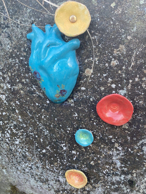 Bright ceramic sculptures stuck to a rock