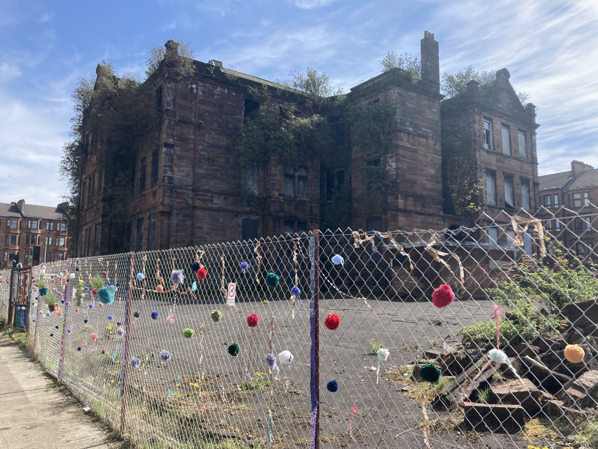 An old dilapidated school in the background, a railing with colourful knitting on it in the foreground