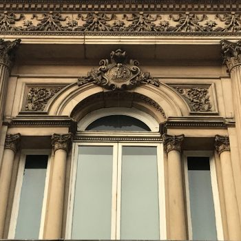 Detail of a 'Palladian' window flanked by columns in a historic neoclassical building.