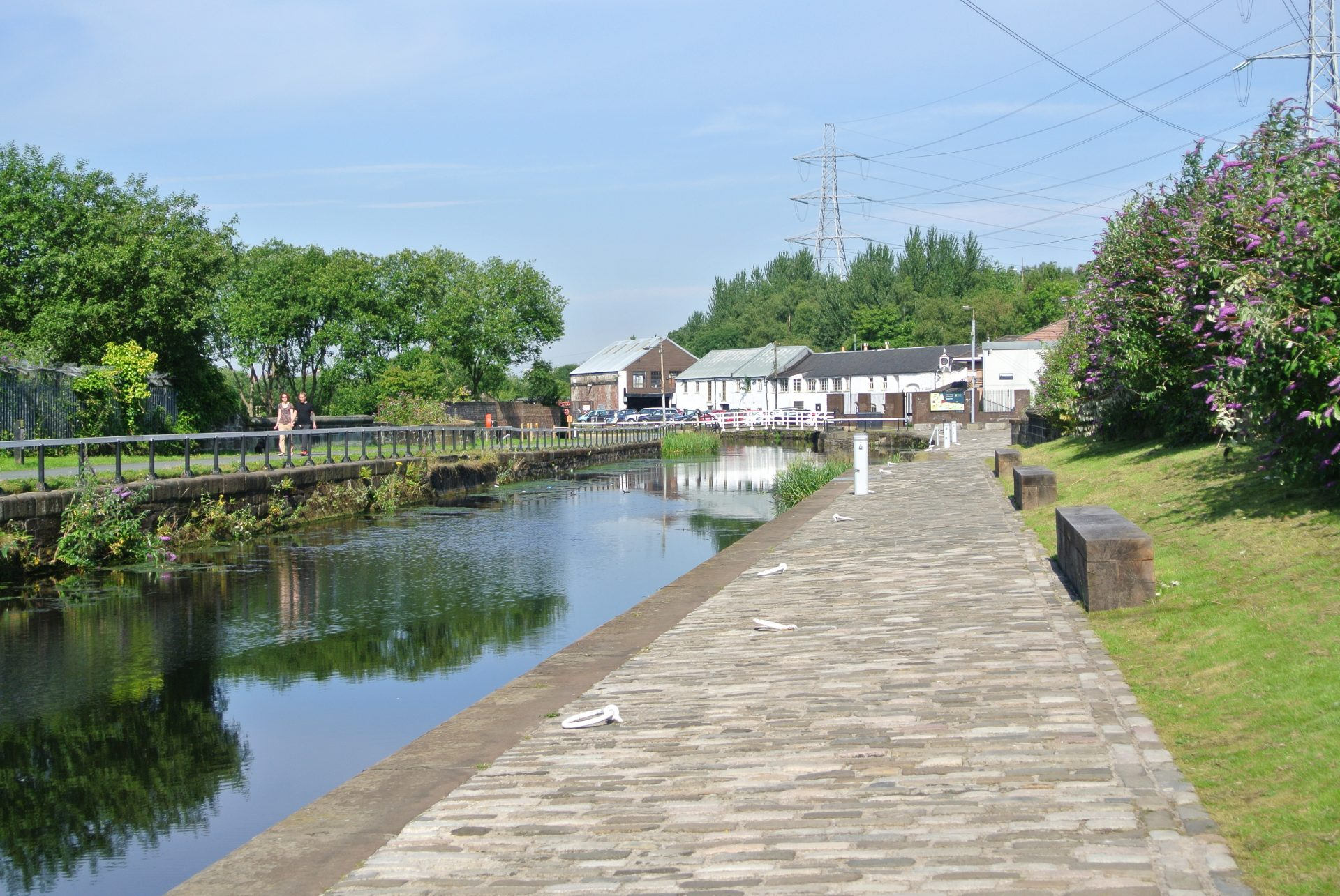 A view of the Forth & Clyde Canal, with towpath in foreground and buildings in the background